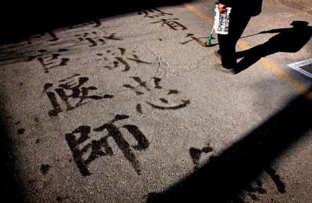مردی با استفاده از آب و یک برس، بر پیادهرویی در مرکز پکن حروف چینی مینویسد