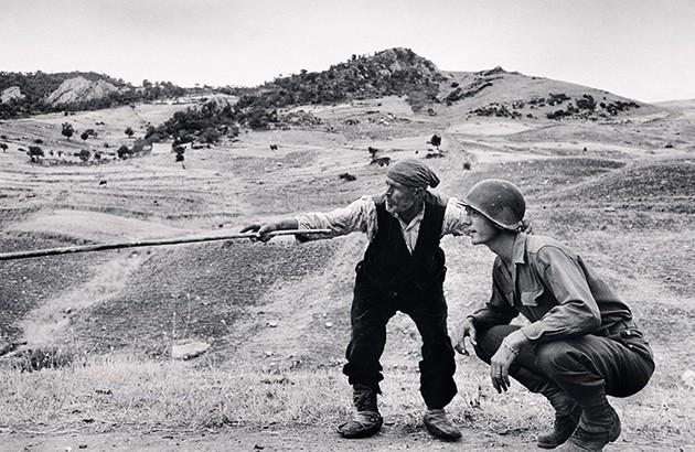 روستایی سیسیلی درحال نشاندادن مسیر حرکت نظامیان آلمانی به یک افسر آمریکایی در جریان جنگ جهانی دوم. عکاس: رابرت کاپا.